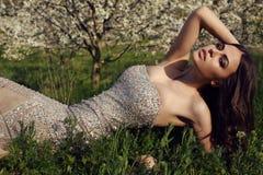 有摆在春天庭院里的黑发的华美的妇女 免版税库存照片