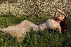 有摆在春天庭院里的黑发的华美的妇女 免版税库存图片