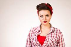 有摆在桃红色背景的针构成和发型的美丽的少妇 免版税库存图片