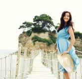 有摆在桥梁的夏天帽子的少妇 免版税图库摄影