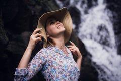 有摆在森林瀑布的帽子的逗人喜爱的妇女 库存图片