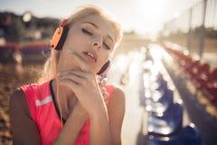 有摆在海滩齐射位子的耳机的年轻美丽的妇女 库存图片