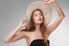有摆在演播室的帽子的美丽的女孩 免版税库存照片