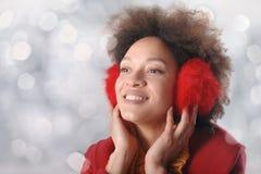 有摆在演播室的御寒耳罩的愉快的少妇 库存照片