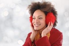 有摆在演播室的御寒耳罩的愉快的少妇 免版税库存照片