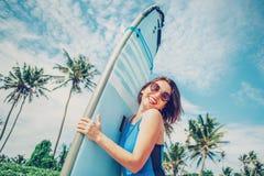 有摆在热带海滩的冲浪板的微笑的妇女 库存图片