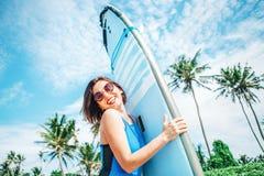 有摆在热带海滩的冲浪板的微笑的妇女 免版税图库摄影