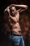 有摆在牛仔裤的完善的身体的赤裸人 免版税库存照片