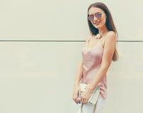 有摆在白色墙壁附近的太阳镜的美丽的时兴地加工好的深色头发的女孩 免版税库存照片