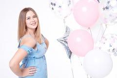 有摆在的气球的愉快的微笑的妇女户内 免版税库存照片