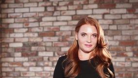 有摆在砖墙附近的自然构成的年轻红发妇女 影视素材