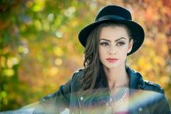 有摆在秋季公园的黑帽会议的美丽的妇女 在秋天期间的年轻深色的消费的时间在森林里 图库摄影