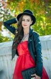 有摆在秋季公园的黑帽会议的美丽的妇女 在秋天期间的年轻深色的消费的时间在森林里 库存照片