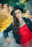 有摆在秋季公园的黑帽会议的美丽的妇女 在秋天期间的年轻深色的消费的时间在森林里 免版税图库摄影