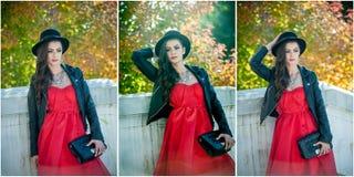 有摆在秋季公园的黑帽会议的美丽的妇女 在秋天期间的年轻深色的消费的时间在森林里 库存图片