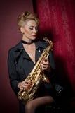 有摆在红色背景的萨克斯管的性感的可爱的妇女 年轻肉欲的白肤金发的使用的萨克斯管 乐器,爵士乐 免版税图库摄影