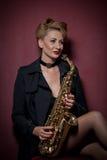 有摆在红色背景的萨克斯管的性感的可爱的妇女 年轻肉欲的白肤金发的使用的萨克斯管 乐器,爵士乐 库存图片