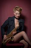 有摆在红色背景的萨克斯管的性感的可爱的妇女 年轻肉欲的白肤金发的使用的萨克斯管 乐器,爵士乐 库存照片