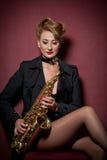 有摆在红色背景的萨克斯管的性感的可爱的妇女 年轻肉欲的白肤金发的使用的萨克斯管 乐器,爵士乐 免版税库存照片