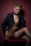 有摆在红色背景的萨克斯管的性感的可爱的妇女 年轻肉欲的白肤金发的使用的萨克斯管 乐器,爵士乐 免版税库存图片