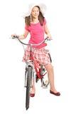 有摆在自行车的一个时髦帽子的女孩 免版税库存照片