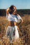 有摆在草甸的亭亭玉立的运动身体身分的可爱的年轻女人 库存图片