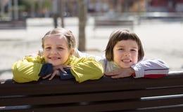 有摆在街道长凳的白肤金发的女孩的男孩在小阳春 免版税库存照片