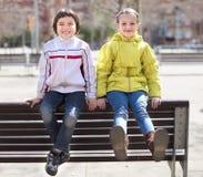 有摆在街道长凳的白肤金发的女孩的男孩在小阳春 图库摄影