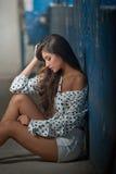 有摆在被解扣的衬衣的,有剥的蓝色油漆老墙壁美丽的女孩在背景 在地板上的俏丽的深色的开会 库存图片