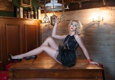 有摆在诱惑说谎在木桌上的短的黑鞋带礼服的可爱和性感的白肤金发的妇女在葡萄酒厨房里 免版税库存图片