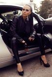 有摆在豪华汽车的黑发的性感的美丽的妇女 库存照片