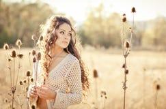 有摆在领域的美丽的卷发的少妇在日落 免版税库存图片