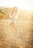 有摆在领域的美丽的卷发的少妇在日落 库存照片