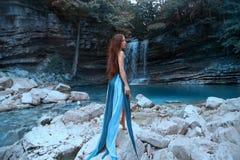 有摆在高瀑布前面的长的豪华健康黑色头发的迷人的女孩在盐水湖用蓝色清楚的水 免版税图库摄影