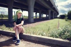 有摆在高速公路路附近的绿色头发的美丽的年轻赃物妇女 免版税库存图片