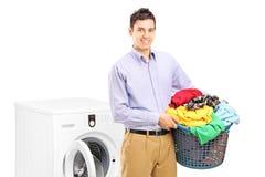 有摆在洗衣机旁边的洗衣店容器的一个微笑的人 库存照片