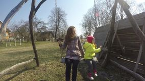 有摇摆在减速火箭的木摇摆的女孩孩子的母亲在早期的春天 股票视频