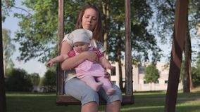 有摇摆在木摇摆的婴孩的母亲在绿色公园外面, wideshot 股票录像
