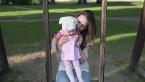 有摇摆在木摇摆的孩子的母亲在绿色公园外面 影视素材