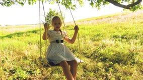 有摇摆在树枝的摇摆的长发的愉快的女孩 在公园愉快的女孩的摇摆 慢的行动 有长期的女孩 影视素材