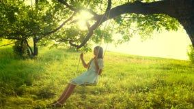 有摇摆在树枝的摇摆的长发的愉快的女孩 在公园愉快的女孩的摇摆 慢的行动 股票视频
