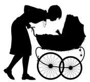 有摇篮车剪影的母亲 免版税图库摄影