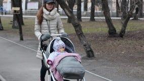 有摇篮车的年轻母亲走在春天公园的 爱和家庭观念 股票录像