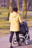 有摇篮车的年轻母亲 免版税库存图片