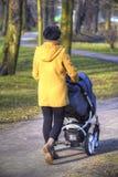 有摇篮车的年轻母亲 图库摄影