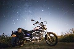 有摩托车的年轻美丽的骑自行车的人妇女在我们的家庭星系Miky方式下星  领域的女性骑自行车的人在晚上 库存图片