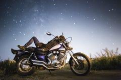 有摩托车的年轻美丽的骑自行车的人妇女在我们的家庭星系Miky方式下星  领域的女性骑自行车的人在晚上 图库摄影