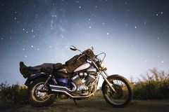 有摩托车的年轻美丽的骑自行车的人妇女在我们的家庭星系Miky方式下星  领域的女性骑自行车的人在晚上 库存照片