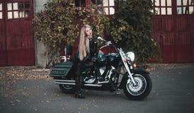有摩托车的美丽的骑自行车的人妇女 库存照片