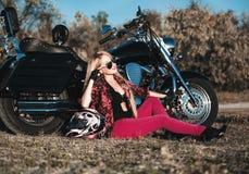 有摩托车的美丽的骑自行车的人妇女 库存图片